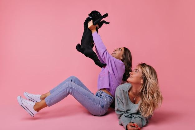 Winnend europees meisje met zwarte franse bulldog. portret van lachende dames spelen met puppy op roze.
