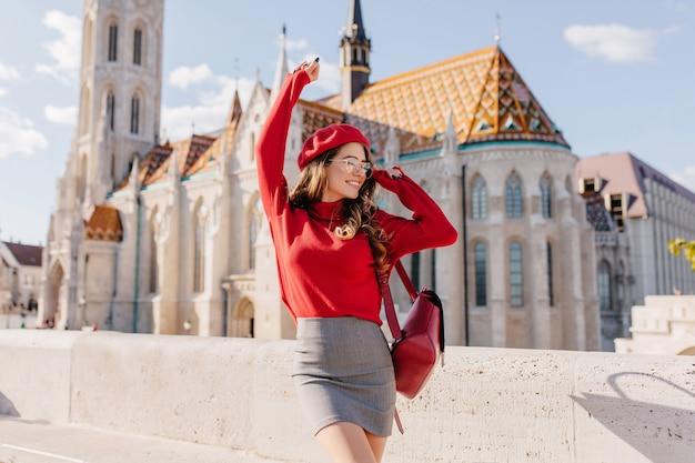 Winnend meisje in grijze rok dansen met blij gezicht expressie met paleis op achtergrond