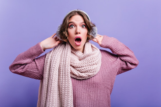 Winnend meisje met donker haar draagt een warme sjaal met open mond verbaasd. indoor close-up foto van krullend geschokt meisje in bont headpones.