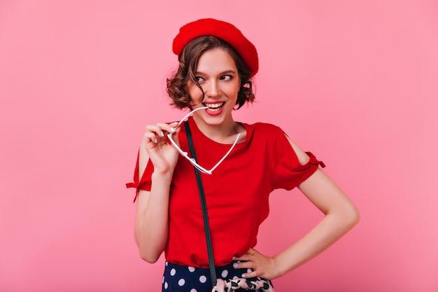 Winnend meisje met krullend kapsel poseren met speelse glimlach. binnen schot van onbezorgde franse dame in rode baret.