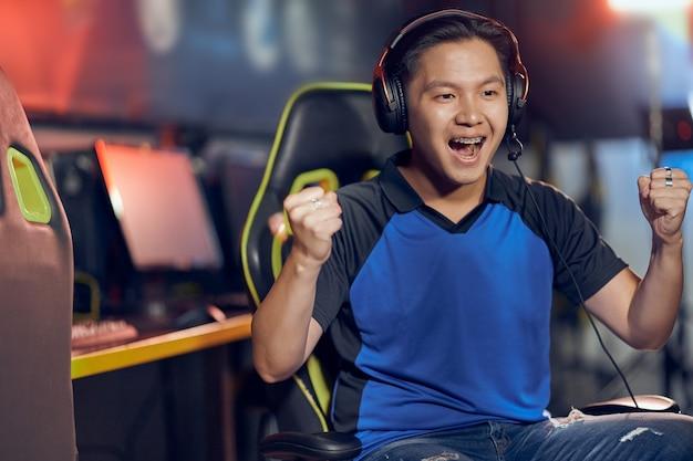 Winnend portret van opgewonden aziatische mannelijke cybersport-gamer die een koptelefoon draagt en naar pc kijkt