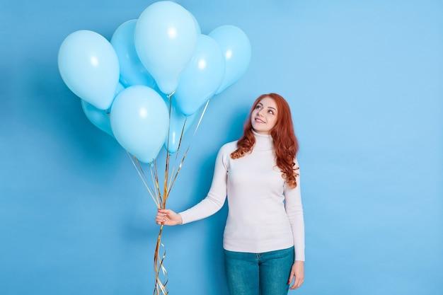 Winnende dame met rood golvend haar poseren in witte trui en spijkerbroek, met veel ballonnen in handen glimlach, verjaardagsverrassing van familie.