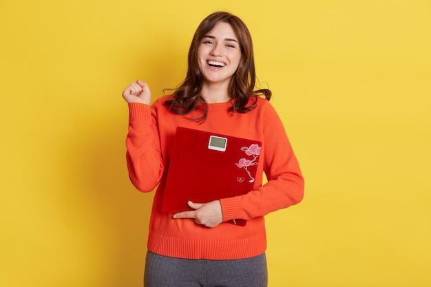 Winnende dame met vloerweegschaal in handen die zich voordeed over geel, gebalde vuist, blij om af te slanken, fijn af te vallen, meisje dat vrijetijdskleding draagt.