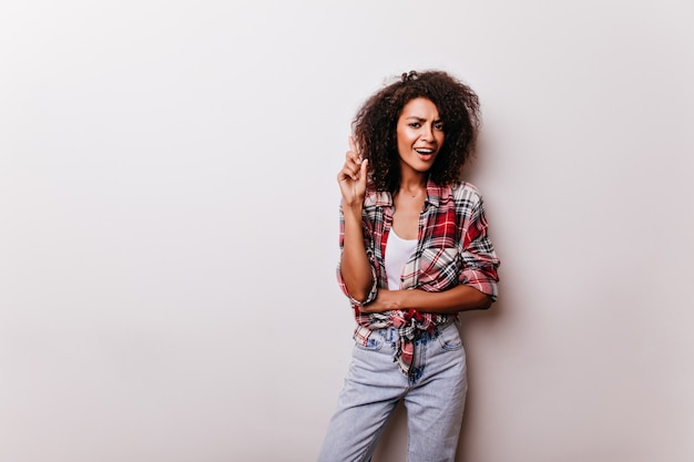 Winnende jonge dame in blauwe spijkerbroek genieten van indoor shotshoot. portret van verfijnde afrikaanse vrouw in rood casual shirt.