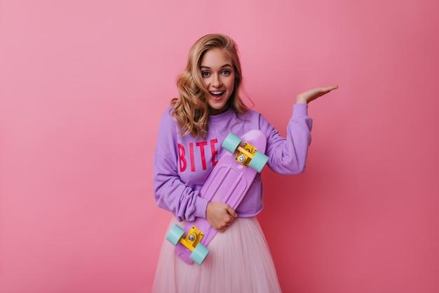 Winnende jonge vrouw in trendy kleding die geluk uitdrukt. extatisch meisje dat met golvend haar paars skateboard houdt.