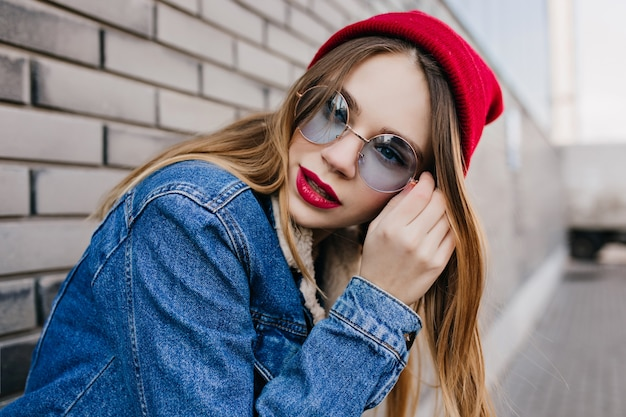 Winnende jonge vrouw met bleke huid poseren in de buurt van bakstenen muur met ernstige gezichtsuitdrukking. buiten foto van modieus meisje in trendy rode hoed koelen op straat.