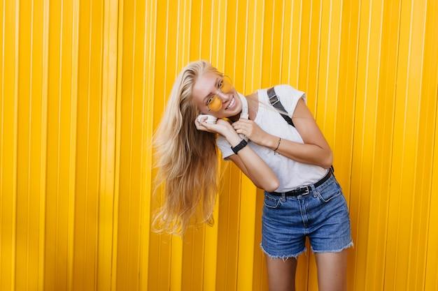 Winnende vrouw in denim shorts poseren met een gelukkige glimlach in de buurt van heldere muur.