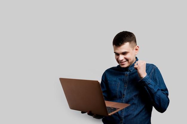 Winnende weddenschap in online casino. gelukkig man met laptop wint een prijs. luxe levensstijl.