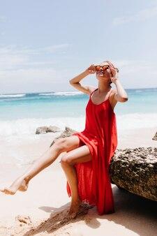 Winsome blanke dame in lange rode kledij chillen op het strand. prachtige gebruinde vrouw die dichtbij oceaan ontspant en op steen stelt.