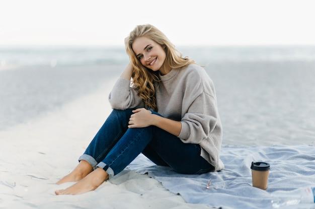 Winsome blanke vrouw koelen op herfst strand. verbazend krullend vrouwelijk model dat van koffie in zand geniet.