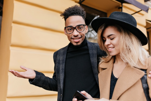 Winsome blonde meisje in hoed op straat lopen met lachende afrikaanse man in zwarte jas. krullend mulat man in glazen praten met zijn europese vriendin geïsoleerd op stad straat.