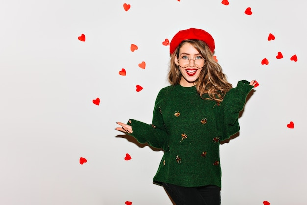 Winsome bruinharige vrouwelijk model in trendy groene trui gek rond op indoor fotoshoot