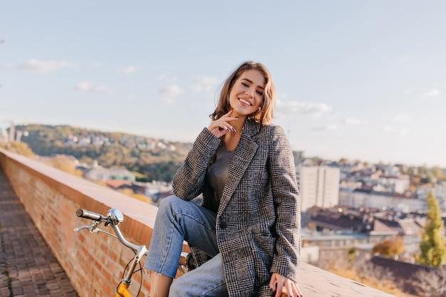 Winsome brunette meisje draagt elegante jas en spijkerbroek die zich voordeed op de achtergrond van de prachtige stad
