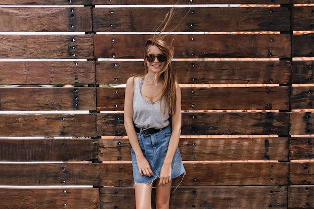 Winsome jonge vrouw in denim rok poseren. mooi wit vrouwelijk model in zonnebril die belangstelling toont.