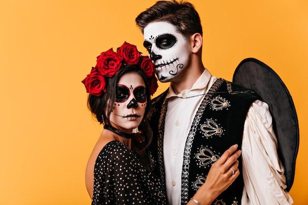 Winsome jonge vrouw in maskerade kostuum poseren op oranje muur. blij dat man in sombrero en halloween-make-up zijn vriendin omhelst.