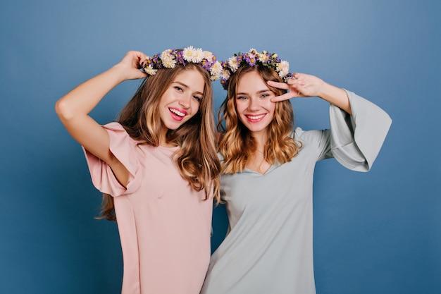 Winsome jonge vrouw in roze kleding met plezier met beste vriend in bloem krans