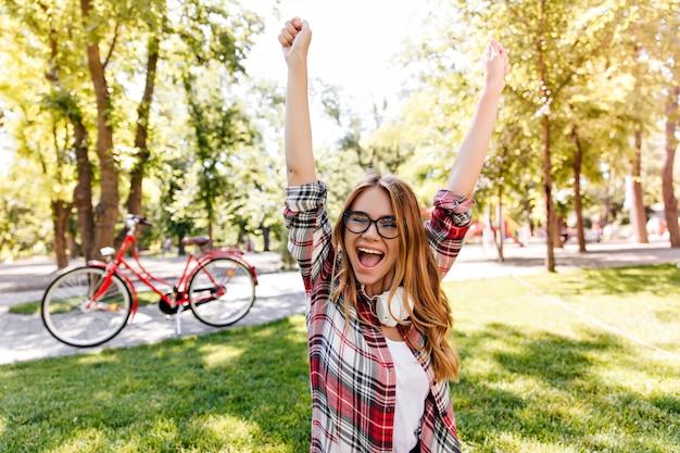 Winsome jonge vrouw opgewonden emoties in park uitdrukken. blij europees meisje in geruit overhemd buiten koelen.