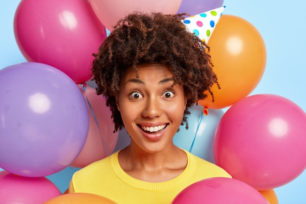 Winsome jonge vrouw poseren omringd door kleurrijke verjaardagsballons