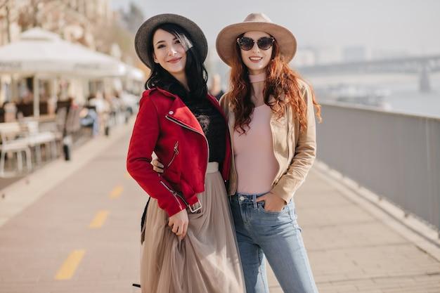 Winsome lachende vrouw in weelderige beige rok en rode jas genieten van vrije tijd met beste vriend
