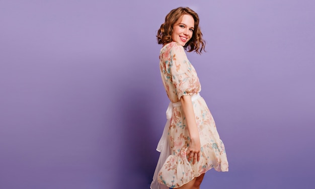 Winsome meisje in romantische kledij vrij glimlachend op paarse achtergrond