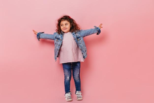 Winsome preteen meisje gelukkige emoties uitdrukken. zalige brunette jongen in spijkerbroek poseren op roze achtergrond.