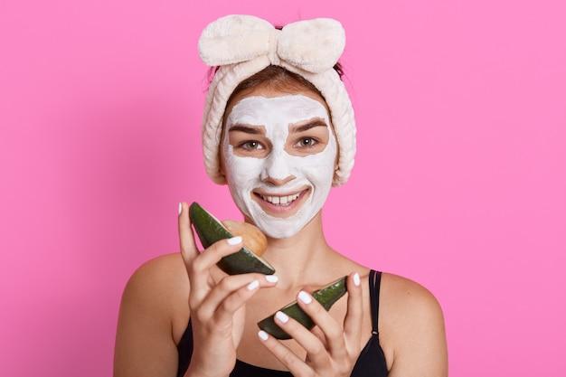 Winsome vrouw bindt haar hoofd terwijl ze avocado in handen houdt, schoonheidsbehandelingen uitvoert, geluk en positieve emoties uitdrukt, staande tegen roze muur.