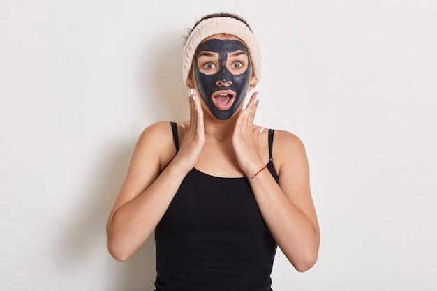 Winsome vrouw die haar huid behandelt en verzorgt. vrouw met haarband op hoofd en gezichtsmasker