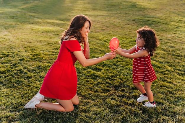 Winsome vrouw in rode jurk spelen met haar dochter in park. buiten foto van lachende jonge dame kijken zusje met glimlach.