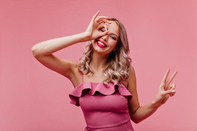 Winsome vrouw met blond golvend haar gek rond op roze muur
