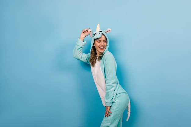Winsome vrouw speels poseren in eenhoorn kostuum
