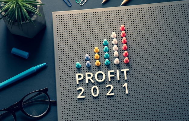 Winst 2021-tekst met pin-graph-grafiek op bedrijfstafel