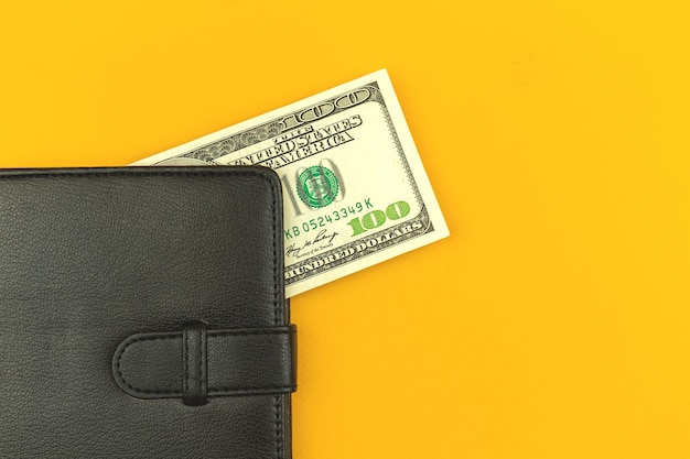 Winst en voordeel met geldconcept, zwart lederen portemonnee met honderd biljetten op kantoorbureaublad, kopieer ruimtefoto