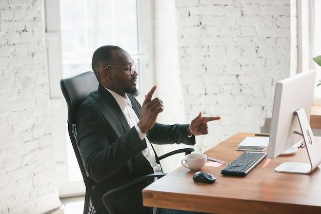 Winst vieren. afro-amerikaanse ondernemer, zakenman die geconcentreerd op kantoor werkt. ziet er gelukkig, vrolijk uit, draagt een klassiek pak, jasje. concept van werk, financiën, zaken, succesleiderschap