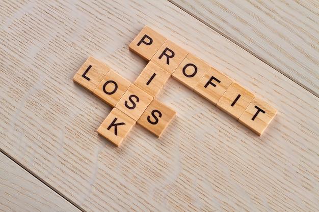 Winstverlies en risico. financiële voorwaarden voor zaken. houten blokken met letters op het houten bureau.