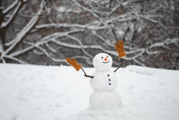 Winter achtergrond met sneeuwvlokken en sneeuwpop. gelukkige sneeuwman met giftdozen die zich in de winter bevinden