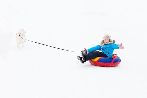 Winter actief plezier - meisje rijdt vanaf de sneeuw heuvel op buizen en een gelukkige hond loopt langszij