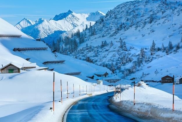 Winter berg landweg met besneeuwde helling (oostenrijk, tirol).