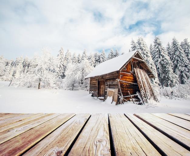 Winter bergen landschap met een besneeuwde bos en een houten hut en armoedige tafel.