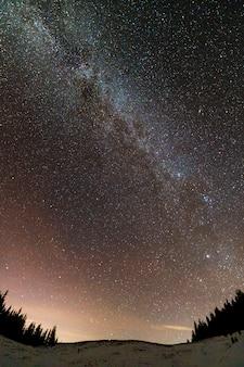 Winter bergen nacht landschap panorama. melkweg helder sterrenbeeld in donkerblauwe sterrenhemel