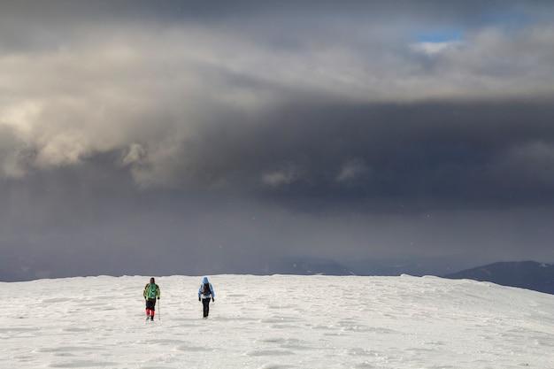 Winter berglandschap. achteraanzicht van reizigers toeristische wandelaars met rugzakken op besneeuwde veld lopen naar verre berg op bewolkte donkerblauwe stormachtige hemel kopie ruimte achtergrond op koude winterdag.