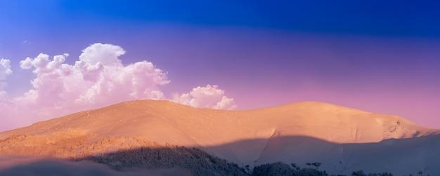 Winter berglandschap. gekleurde dageraad over de met sneeuw bedekte bergen. drone-weergave.