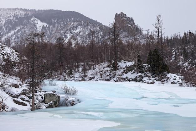 Winter berglandschap met rivier bedekt met blauw ijs, in zachte kleuren