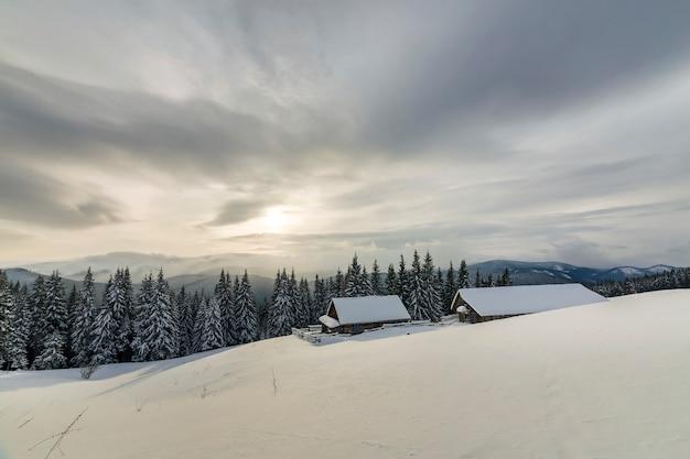 Winter berglandschap. oude blokhuizen op sneeuwopheldering van bergrand, nette bos en bewolkte hemel. gelukkig nieuwjaar en merry christmas-kaart.