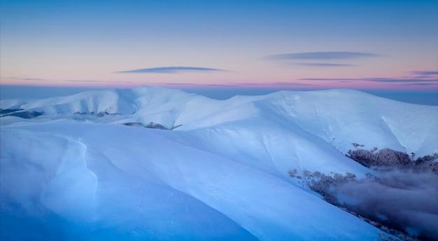 Winter berglandschap. uitzicht op de dageraadhemel vanaf de berg gimba.