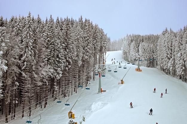 Winter besneeuwd bos en een stoeltjeslift voor skiërs