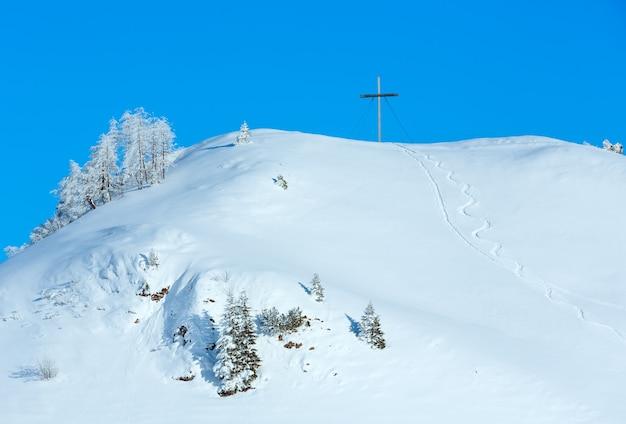 Winter besneeuwde heuvel met kruis bovenop.
