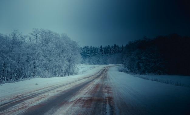 Winter besneeuwde weg. takken met besneeuwde bomen hangen over de weg. winterlandschap. reis in de winter.