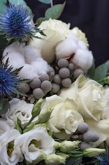 Winter bruiloft boeket van witte rozen, katoen en eringium op een zwart. het boeket van de bruid.