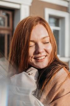 Winter buiten portret van een roodharige vrouw in natuurlijke tinten. jonge vrouw die van het leven geniet