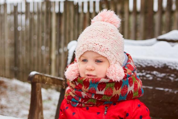 Winter buiten portret van schattige dromerige babymeisje in gebreide muts en sjaal. leuk speels meisje buiten genietend van de eerste sneeuw